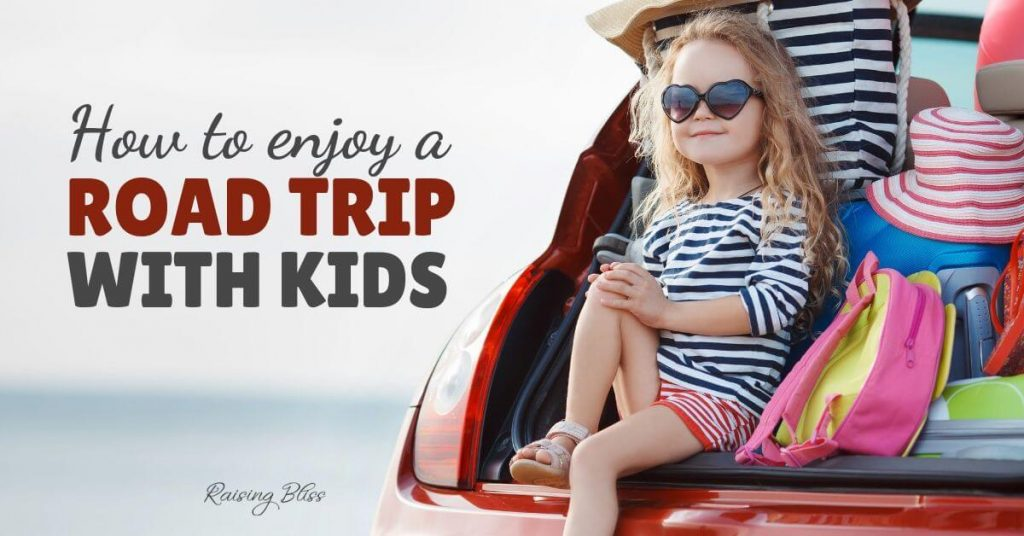 Little girl sitting in the trunk of a car with suitcases. How to enjoy a road trip with kids by raising bliss