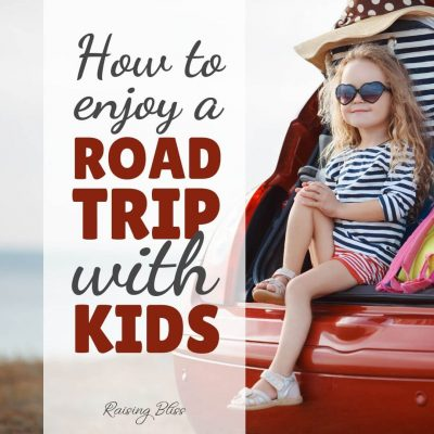 Little girl sitting in the back of a car packed for a trip. How to enjoy a road trip with kids by raising bliss