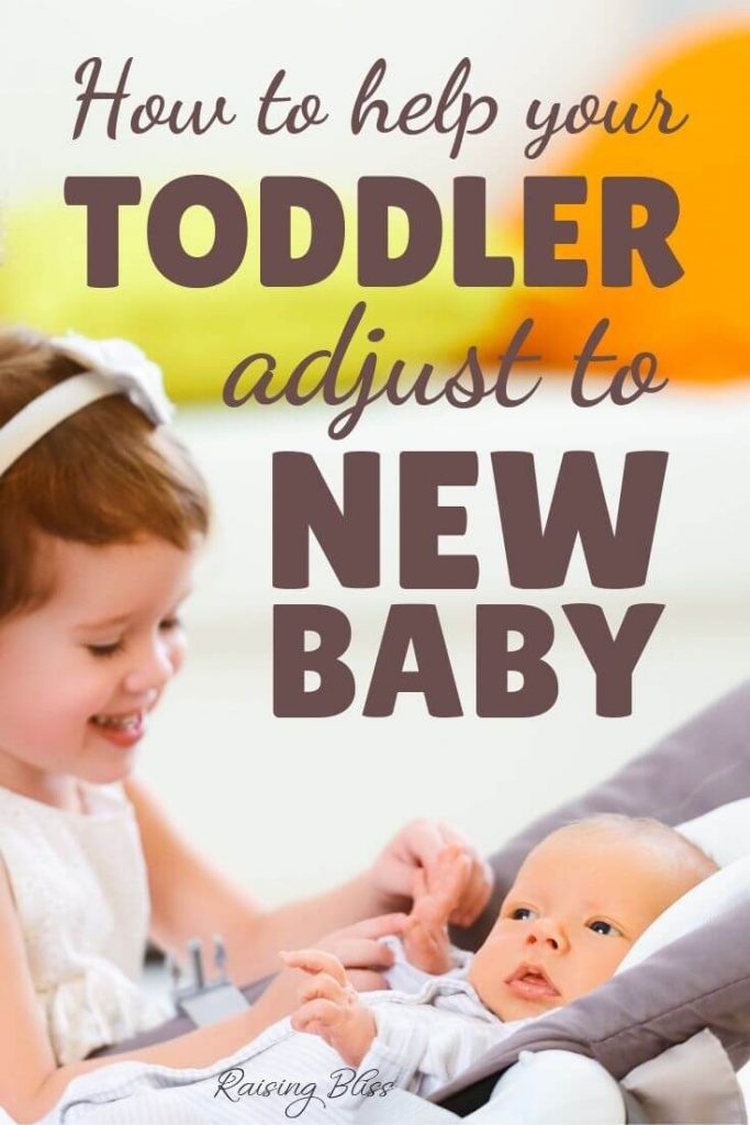 Little girl playing with newborn sibling - How to help your toddler adjust to new baby by Raising Bliss