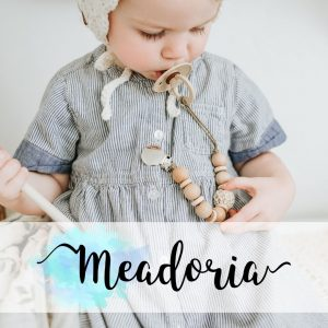 Meadoria is a sister brand of raising bliss. Baby in a bonnet with a pacifier clip