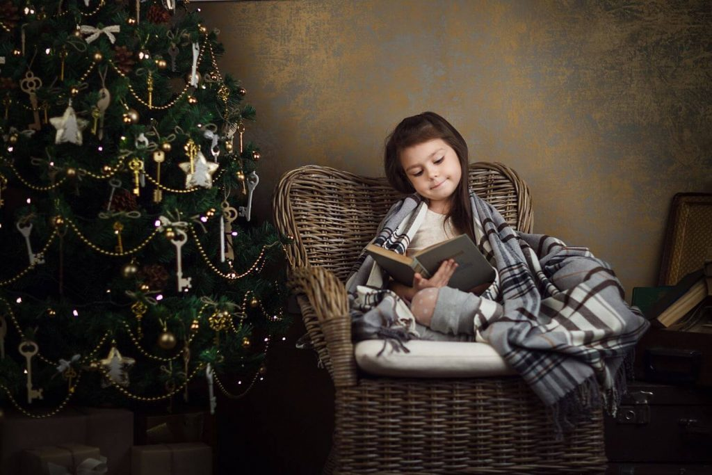 Young Girl reading a book by the christmas tree